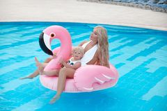 Beauty fashion mother with daughter family look. Beautiful blond. Women with having fun with little pretty gil wears in swim wear posing on Inflatable Flamingo royalty free stock photo