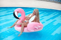 Beauty fashion mother with daughter family look. Beautiful blond. Women with having fun with little pretty gil wears in swim wear posing on Inflatable Flamingo stock photography