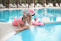 Beauty fashion mother with daughter family look. Beautiful blond. E pretty women having fun with adorable little girl wears in white swimwear having fun by royalty free stock photo