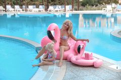 Beauty fashion mother with daughter family look. Beautiful blond. E pretty women having fun with adorable little girl wears in white swimwear having fun by royalty free stock image