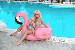 Beauty fashion mother with daughter family look. Beautiful blond. Women with having fun with little pretty gil wears in swim wear posing on Inflatable Flamingo royalty free stock photography