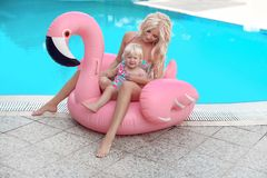 Beauty fashion mother with daughter family look. Beautiful blond. Women with having fun with little pretty gil wears in swim wear posing on Inflatable Flamingo royalty free stock image