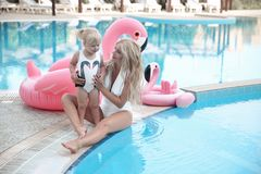 Beauty fashion mother with daughter family look. Beautiful blond. E pretty women having fun with adorable little girl wears in white swimwear having fun by royalty free stock images