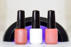 Beauty, fashion and Nail art concept. Manicure art cosmetic tools uv lamp and three bottles pink white beige gel nail polish. with. Beauty, fashion and Nail art royalty free stock photos
