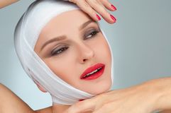 Beautiful woman after plastic surgery with bandaged face. Beauty and Fashion Stock Image