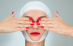 Beauty, Fashion and Plastic Surgery concept. Woman covering eyes with bandaged head Royalty Free Stock Image