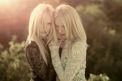 Beauty fashion portrait. Contrasts and opposites concept. Sisters twins posing on sunny natural landscape. Dualism and dualistic nature. Two women with red royalty free stock images