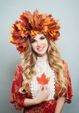 Beauty fashion portrait of pretty autumn woman in bright fall leaves crown with red maple leaf.  royalty free stock photography