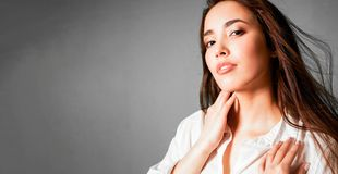 Beauty fashion portrait of sensual asian young woman with dark long hair in white shirt on grey background, banner stock image