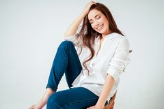 Beauty fashion portrait of smiling sensual asian young woman with dark long hair in white shirt sitting on chair on white stock photos