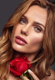 Young model with natural makeup and perfect skin. Beauty fashion portrait of young blond woman model with natural makeup and perfect skin with beautiful rose royalty free stock photos