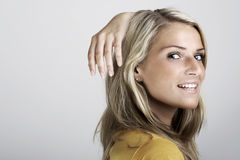 Beauty fashion portrait of a young blond woman. Smiling and holding the hand high behind the head Stock Photo