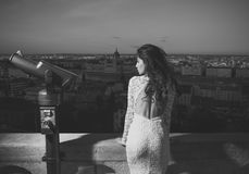 Beauty fashion portrait. Young girl in white dress look with binoculars on city skyview. Woman with touristic telescope.  Royalty Free Stock Images