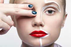 Beauty fashion portrait of a young woman. Female with an unusual creative makeup face paintin stock photography