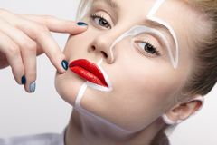 Beauty fashion portrait of a young woman. Female with an unusual creative makeup face paintin royalty free stock photography