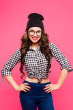 Beauty fashion girl wearing glasses, pink background, hipster outfit, hat, plaid shirt, jeans, smiling white teeth Stock Photo