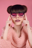 Beauty Fashion teen girl model in heart sunglasses. Portrait of. Brunette with matte lips makeup and hairstyle posing over studio pink background Royalty Free Stock Photos