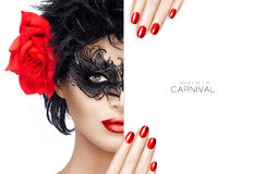 Beauty Fashion Woman with Carnival Mask Makeup. Red Lips and Man. Front close up view on beautiful woman in short black hair, carnival mask and large rose royalty free stock photography
