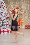Beauty fashion woman Christmas background new year tree. Vogue style sexy girl. Gorgeous female in luxury dress at Xmas. Party. Luxury life concept. Retro style Royalty Free Stock Photos
