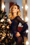 Beauty fashion woman Christmas background new year tree. Vogue style sexy girl. Gorgeous female in luxury fur at Xmas Stock Image