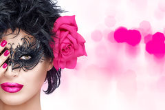 Beauty Fashion Woman with Elegant Mask. Pink Lips and Manicure. Beauty model girl with stylish black carnival mask and Big Rose Flower. Pink Lips and Manicure Royalty Free Stock Image
