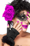 Beauty Fashion Woman with Elegant Mask. Purple Lips and Manicure. Glamorous beauty model wearing creative masquerade eye makeup and big purple rose flower on ear Royalty Free Stock Image