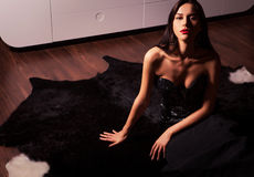 Beauty fashion Women Portrait. Model pose in luxury dress on black fur. Royalty Free Stock Photo