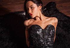 Beauty fashion Women Portrait. Model pose in luxury dress on black fur. Stock Photo