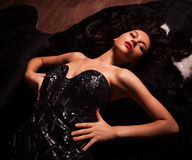 Beauty fashion Women Portrait. Model pose in luxury dress on black fur. Stock Photography