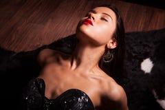 Beauty fashion Women Portrait. Model pose in luxury dress on black fur. Royalty Free Stock Photo