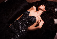 Beauty fashion Women Portrait. Model pose in luxury dress on black fur. Royalty Free Stock Images