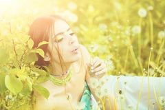 Beauty and fashion, youth and freshness . girl with fashionable makeup and beads in green leaves. Beauty and fashion, youth and freshness. blowing dandelion Stock Image