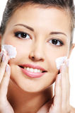 Beauty female apply cosmetic cream. Close-up portrait of a happy young female face with a cosmetic cream on cheek royalty free stock photos