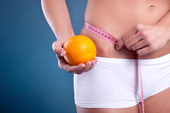 Beauty female body with measuring tape and orange Royalty Free Stock Photos