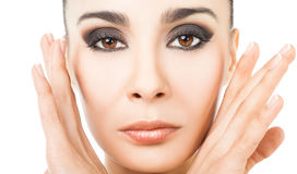 Beauty female face. Close-up of beautiful female with hands next to face, looking at camera royalty free stock image