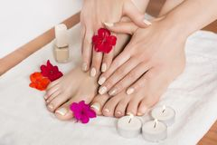 Women feet and hands with french manicured nails and flowers and candles on white towel. Beauty female feet and hands at spa salon on pedicure and manicure royalty free stock photography