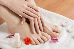 Female feet and hands with beautiful pedicure and manicure after spa procedure and flowers and candle on towel. Beauty female feet and hands at spa salon on royalty free stock photos