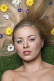 Beauty female with flowers. Close-up beauty portrait of blonde woman with perfect skin and long smooth hair lying on garden with some colourful flowers in the Stock Photo
