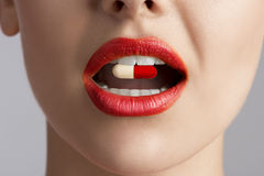 Beauty female lips with pill. Close-up of beauty female mouth with coloured pill between teeth Royalty Free Stock Image