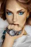 Beauty female with watch on hand looking at camera Royalty Free Stock Image