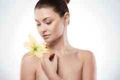 Beauty of femininity. Natural young woman with lily on the arm Royalty Free Stock Photography