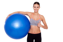 Beauty with fitness ball. Portrait of attractive adult woman holding fitness ball and smiling at camera with thumb up Royalty Free Stock Photography