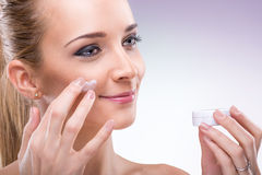 Beauty flawless skinned woman with face cream. Beauty flawless skinned woman with face cream Stock Photography