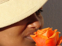 Beauty in a flower. African Lady with an orange rose and a hat Stock Photography
