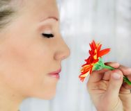Beauty flower. A woman with blue eyes and a gerbera flower in front of her head - beauty flower Stock Photography