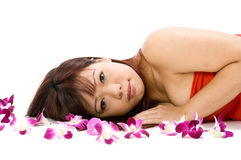 Beauty and Flowers. A young Asian woman lying on the floor with purple orchid flowers Royalty Free Stock Photo