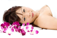 Beauty with Flowers. A young Asian woman lying on the floor with purple orchid flowers Royalty Free Stock Photo