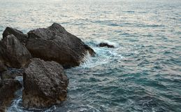 Beauty and force of deep water. Danger o swimming in forbidden places. Wild sea panorama surrounded with sharp rock stones in royalty free stock images