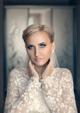 Beauty fresh blonde woman with beautiful blue eyes in white bridal dress posing Stock Photo