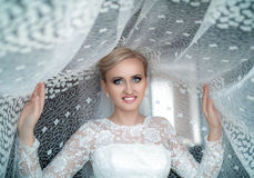 Beauty fresh blonde woman with beautiful blue eyes in white bridal dress posing. Bride in a white dress, blue eyes Royalty Free Stock Photography